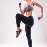 Young attractive fitness model girl woman make different aerobics exercises with dumbbells isolated on white background dressed up in sportswear shadows