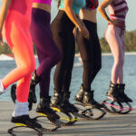 Beautiful women in sportswear jumping in a kangoo jumps shoes at the street on summer's sunny day. Jumping high, active movement, action, fitness and wellness. Fit female models during training.