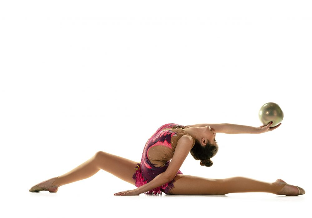 Young flexible girl isolated on white studio background. Teen-age female model as a rhythmic gymnastics artist practicing with equipment. Exercises for flexibility, balance. Grace in motion, sport.